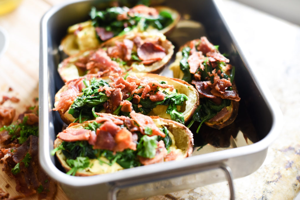 A fun, hand held breakfast option: Crispy Breakfast baked potato skins topped with scrambled eggs, garlicky spinach, chopped, crispy bacon, and a dollop of fresh pesto. Plus, tons of ways to customize and change things up!