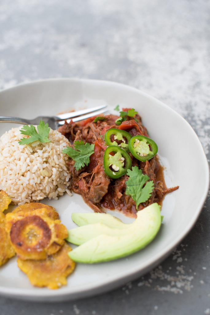 bowl with shredded Ropa Vieja, fried plantains, and a serving of rice on a gray table