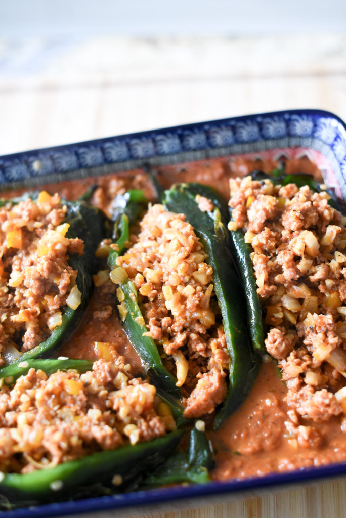 Enchilada Stuffed Poblano Peppers: Fire roasted poblano peppers, deseeded and stuffed with a delicious chorizo filling packed with onions, garlic, bell peppers, and cauliflower rice. They are then nestled into a smoky enchilada sauce and baked till bubbly.