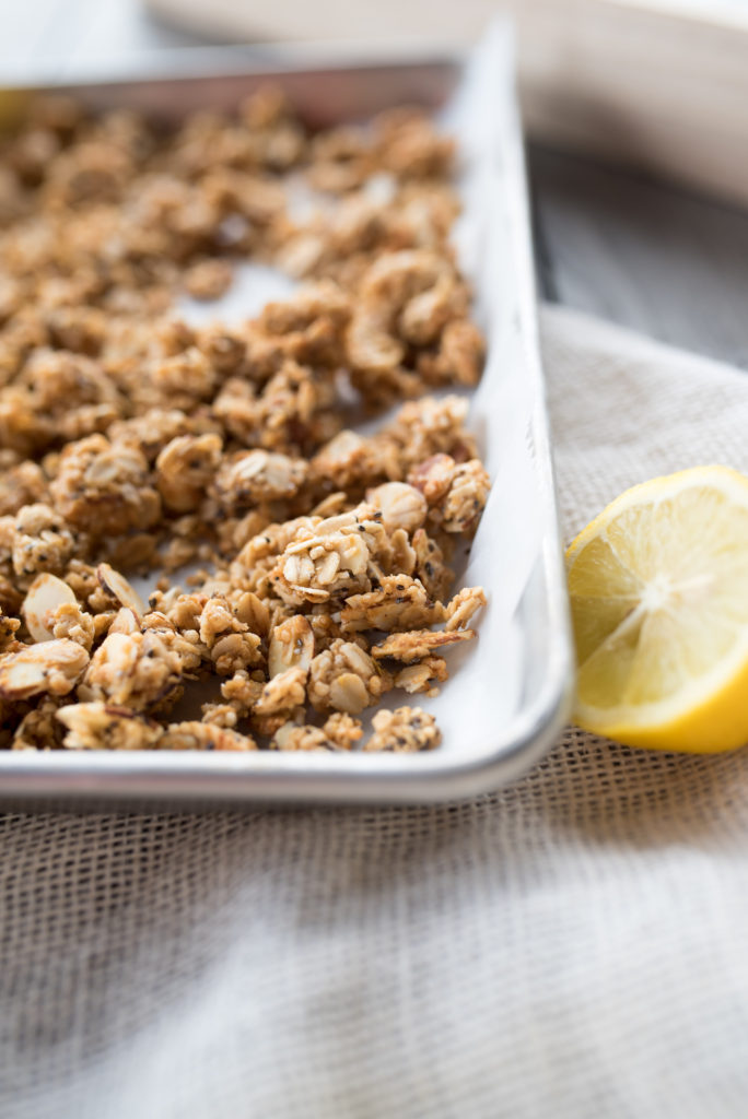 Close up of Lemon Chia Seed Granola on a tray with a halved lemon.