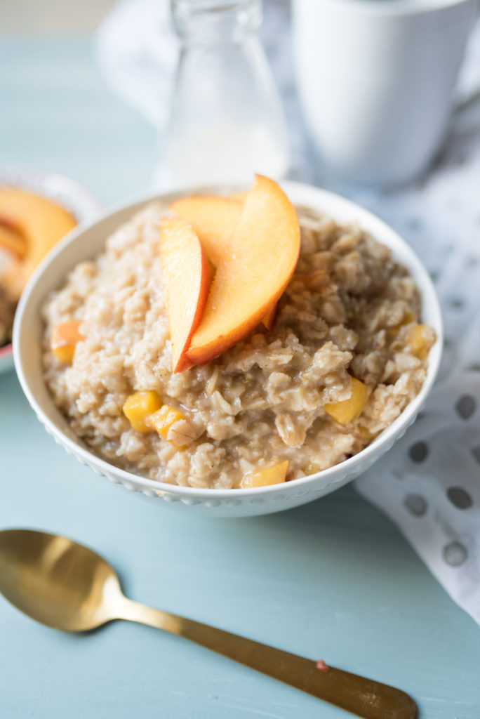 Sweet and Creamy oatmeal with ripe peaches sautéed in brown sugar and a healthy drizzle of cream at the end. A decadent breakfast in a bowl.