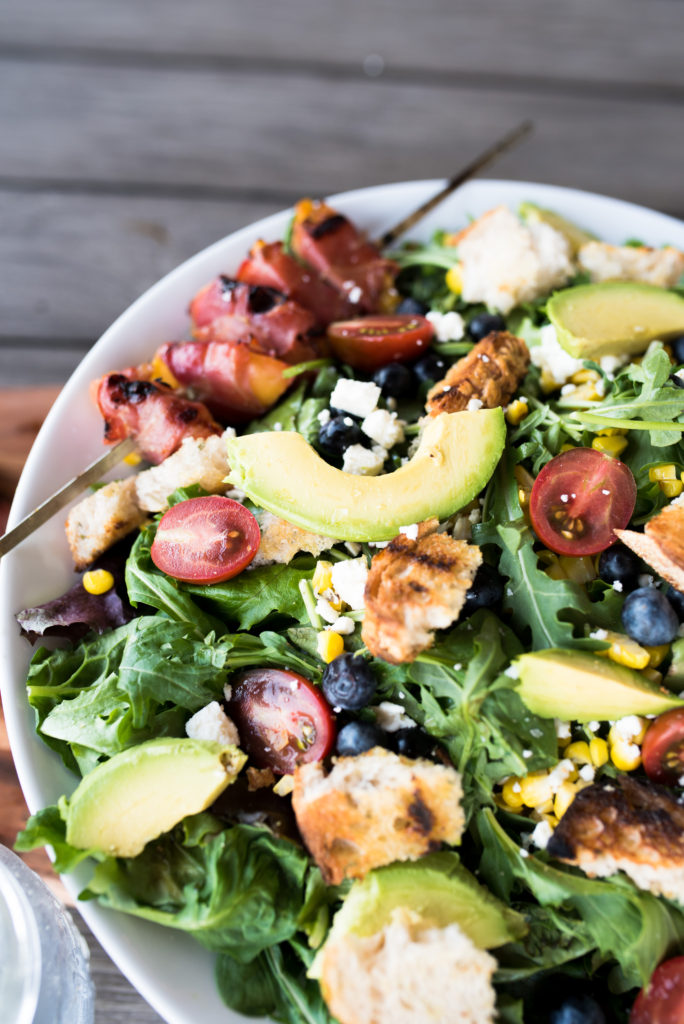 This Grilled Prosciutto wrapped peach panzanella salad is a light and delicious summer salad with grilled prosciutto-wrapped peaches, sweet blueberries, crumbled feta, grilled sourdough and charred corn.