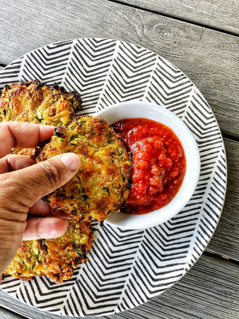 Zucchini fritters being dipped into marinara sauce