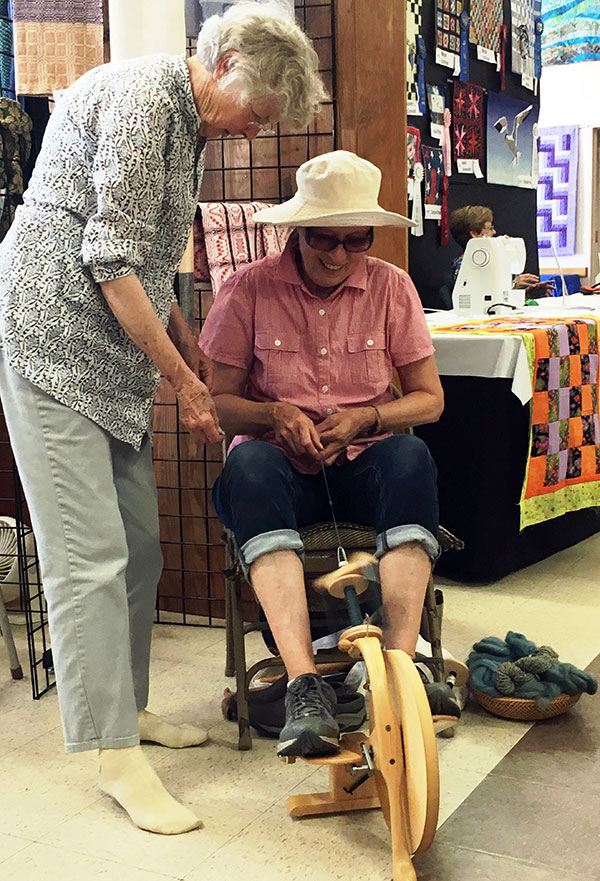 Cecelia teaching spinning at the Fair