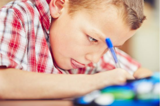 Little boy writing, concentrating hard, head close to paper
