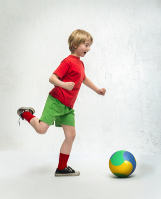 smiling blond boy with visual processing disorder (VPD) plays soccer in red shirt, green shirt