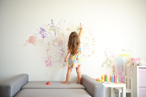 Toddler girl paints the wall of her bedroom