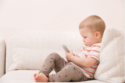 Toddler playing with toy mobile phone
