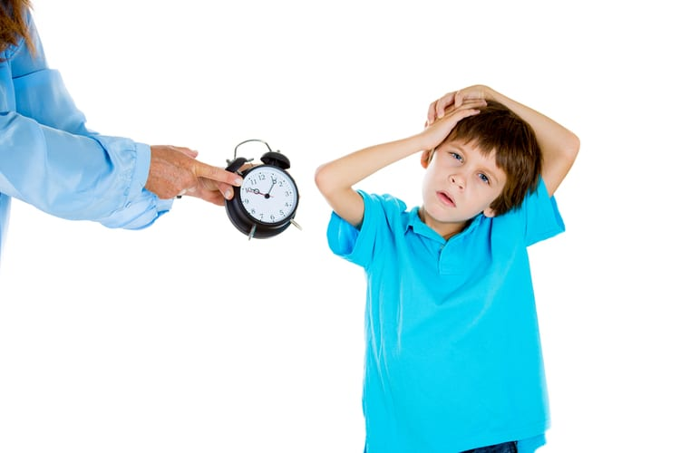 Mother showing tired boy with ADHD symptoms that it's time to go to bed