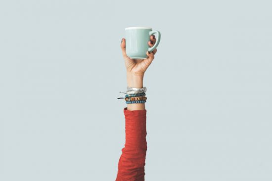 Arm holding up coffee cup