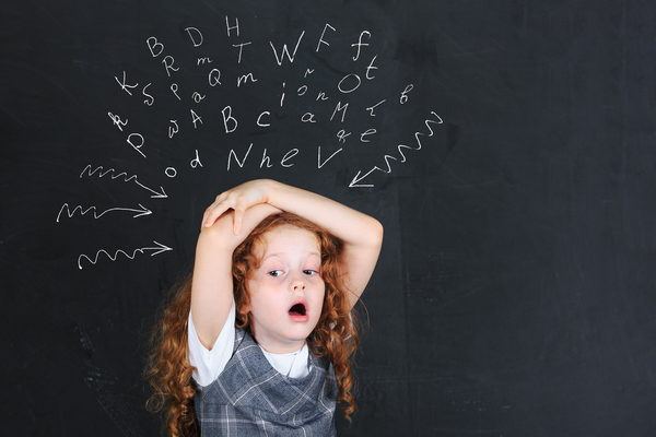 Girl with dysgraphia thinking letters