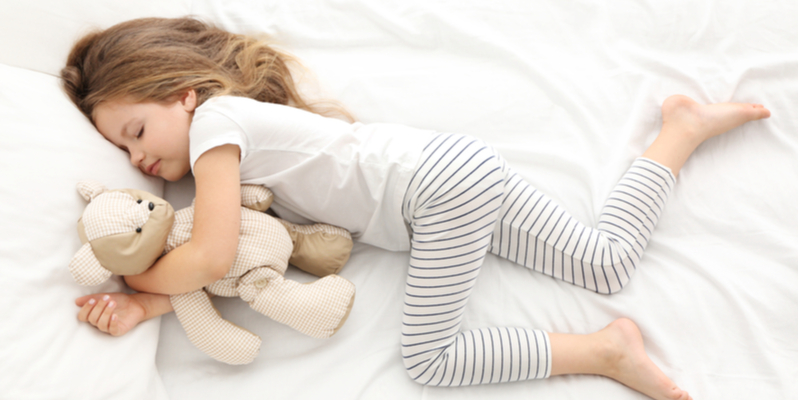 child asleep in bed with teddy bear