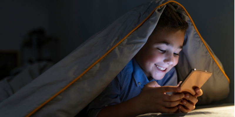 child with smartphone texting under covers at night