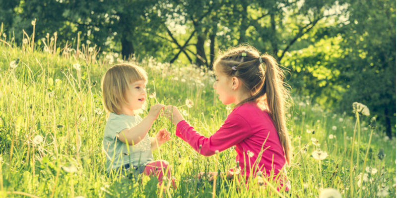 sisters playing in field in morning sun