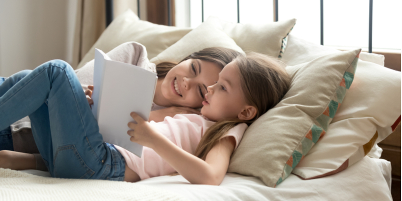 smiling calm mother and daughter reading together in bed