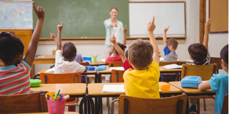 Smiling teacher kids with raised hands in classroom