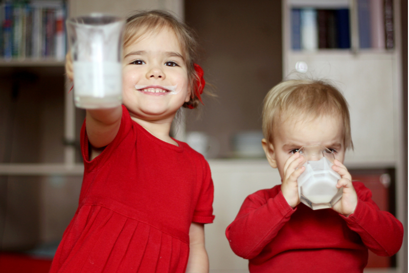 Happy boy and girl drink whole milk