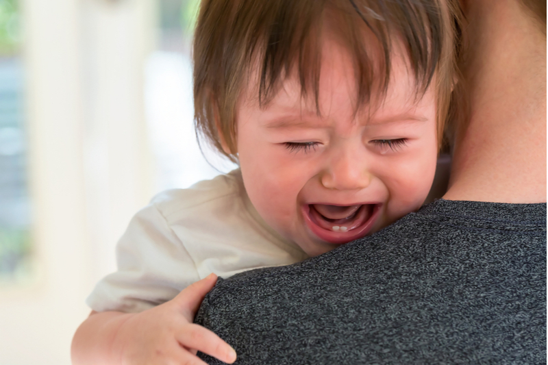Calm mother is managing emotions as she holds her crying child