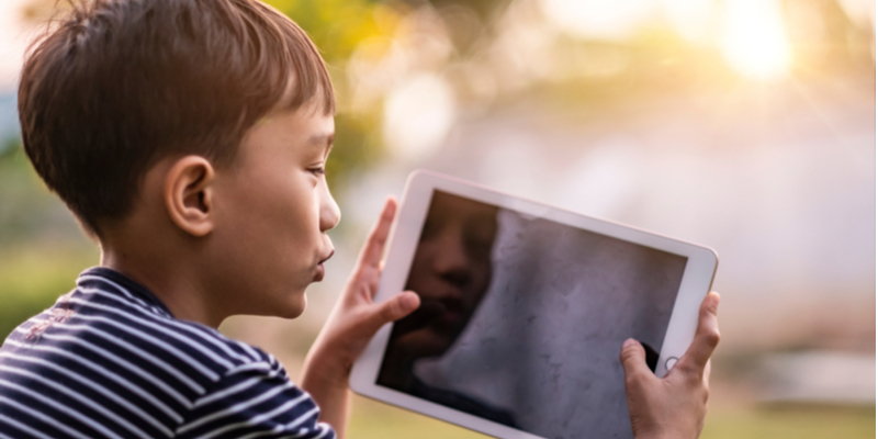 Asian boy has virtual fun on tablet with friend to counter coronavirus isolation