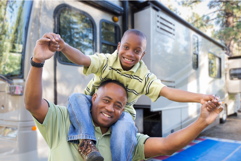 African American father with son on shoulders in front of RV
