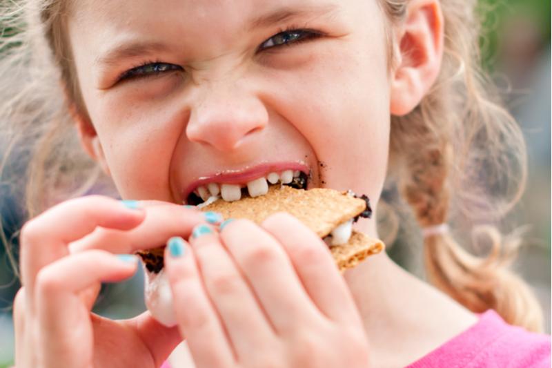 little girl eats s'more