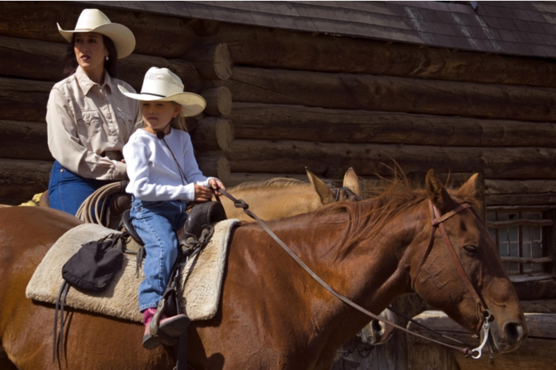 mother and daughter ride horses in Montana