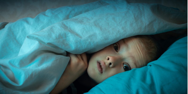 frightened child having nightmares peeks out from under the covers