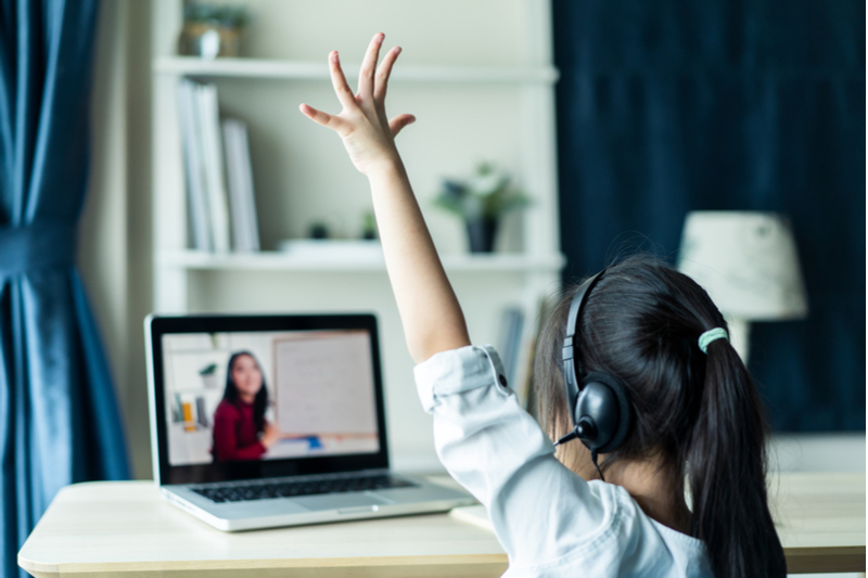 little girl raises hand in remote classroom