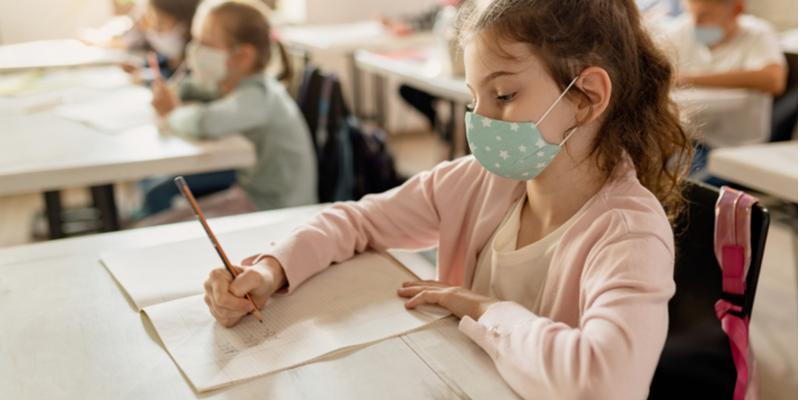 masked schoolgirl does schoolwork back to school 2020