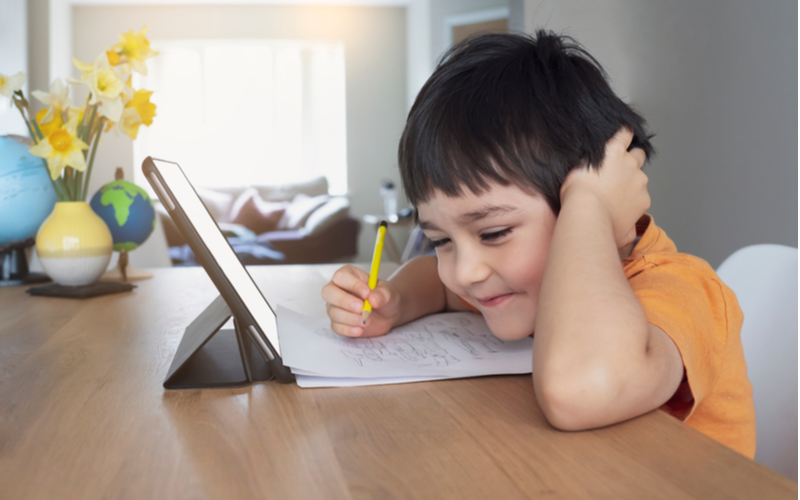The little boy happily taking notes while using tablet illustrates educational term blended learning