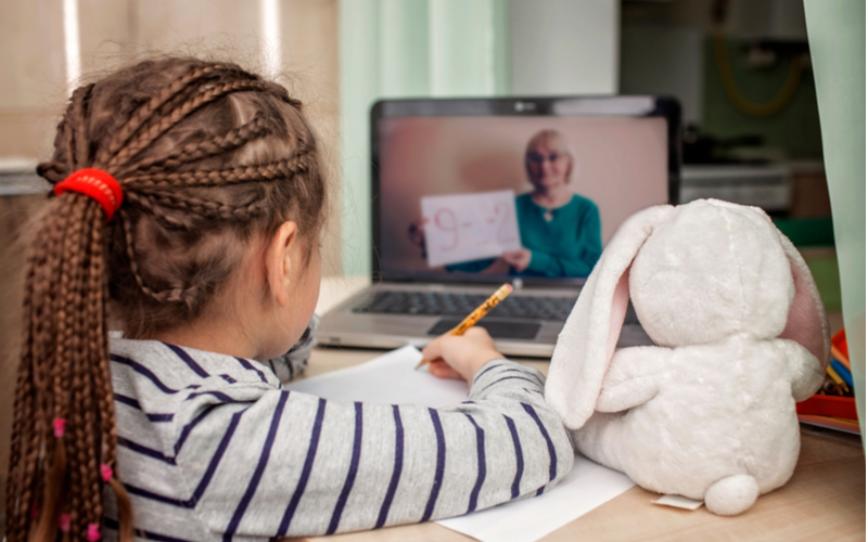 "Little girl takes online class with teacher illustrating the educational term ""synchronous learning"""