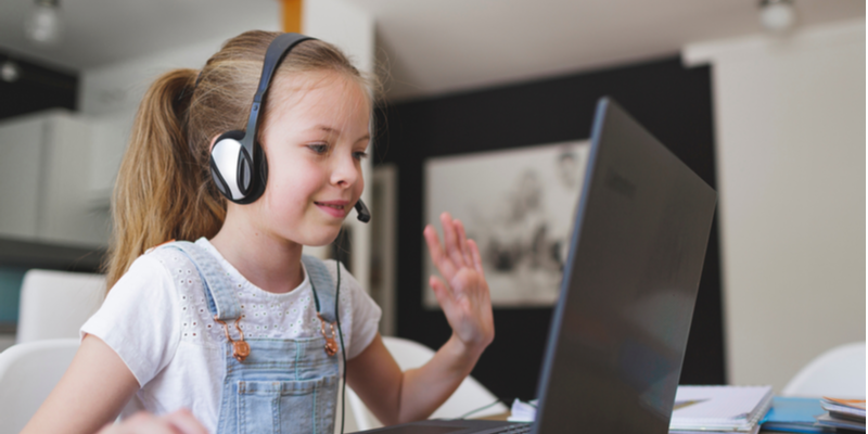 pretty young girl waves to friend on screen while wearing headset