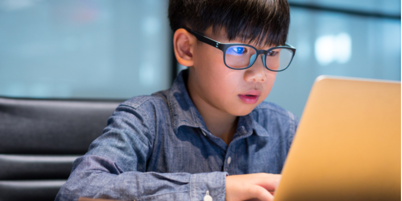 studious preteen asian boy blue light reflected in glasses from screen time