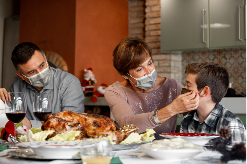 holiday visits 2020: parents adjust mask on son at festive meal