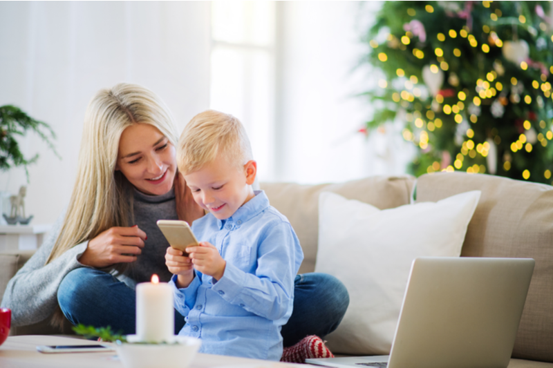 Smiling Mom and little blond boy watch phone video