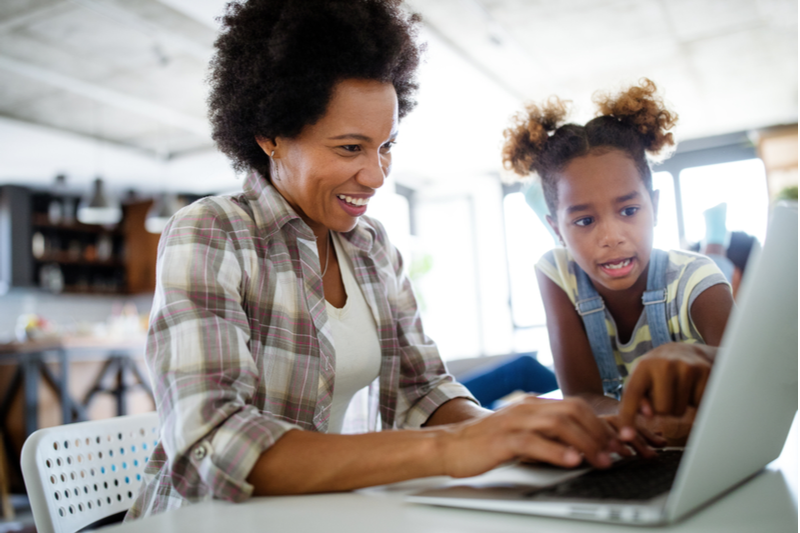 african american daughter shows smiling mom how to use computer program on laptop