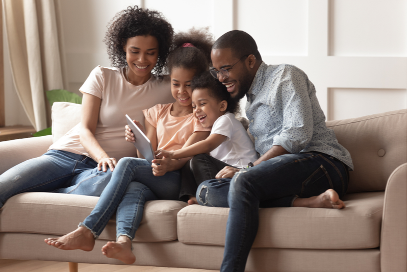 laughing african american family stays connected as they enjoy time on tablet together on sofa