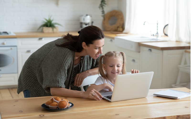 mother guides daughter on laptop