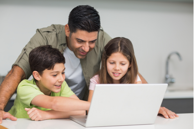 smiling dad stays connected to kids as they demonstrate something on laptop