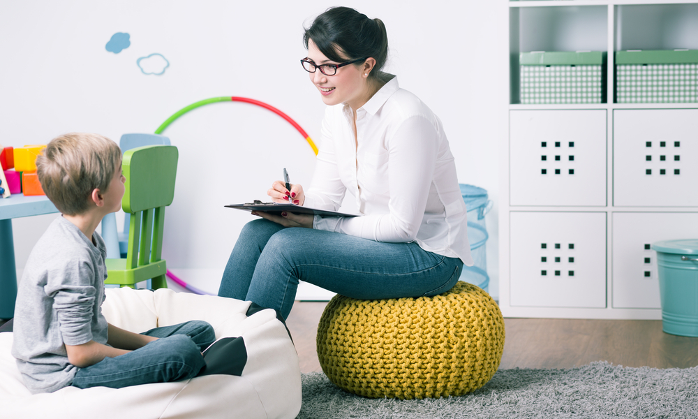 Smiling therapist sits on pouf, works with young boy