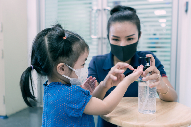 Masked mom helps masked daughter use hand sanitizer against the spike in child cases of COVID19