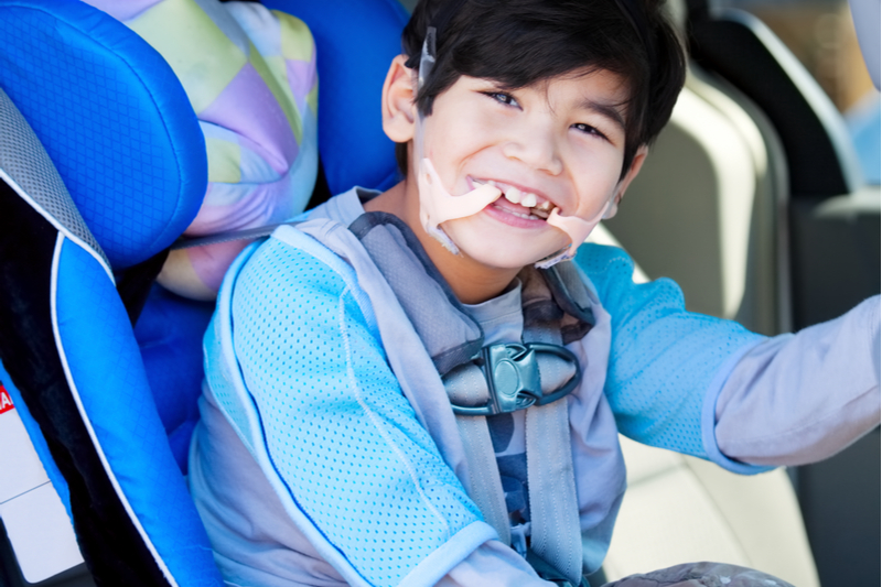 special needs child in car seat ready for a family road trip