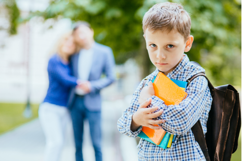 proud parents in background as young boy wrestles with back to school fears