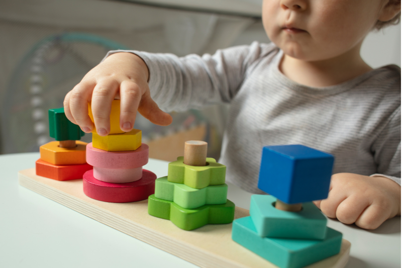 beautiful toddler plays wooden toys home