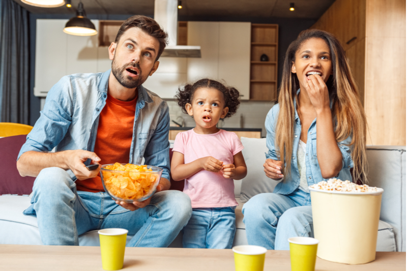 biracial family watches tv while snacking