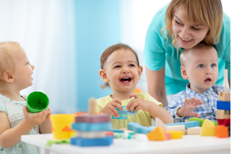pandemic babies play with teacher in day care