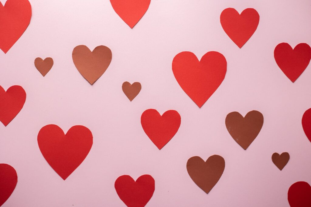 paper hearts of different size pinned on pink surface