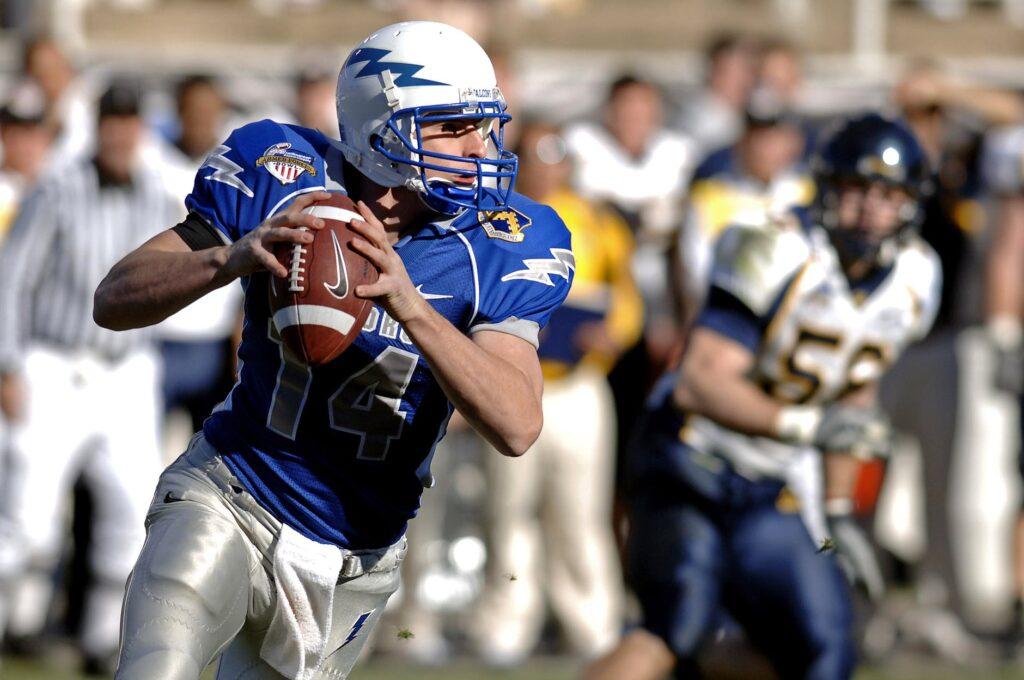 selective focus photography of man holding nike football ball