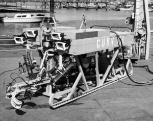 A black and white photograph of a boxy remotely operated vehicle with a grasping claw at the front