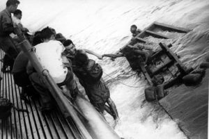 Survivors of torpedo ship are helped to safety from water